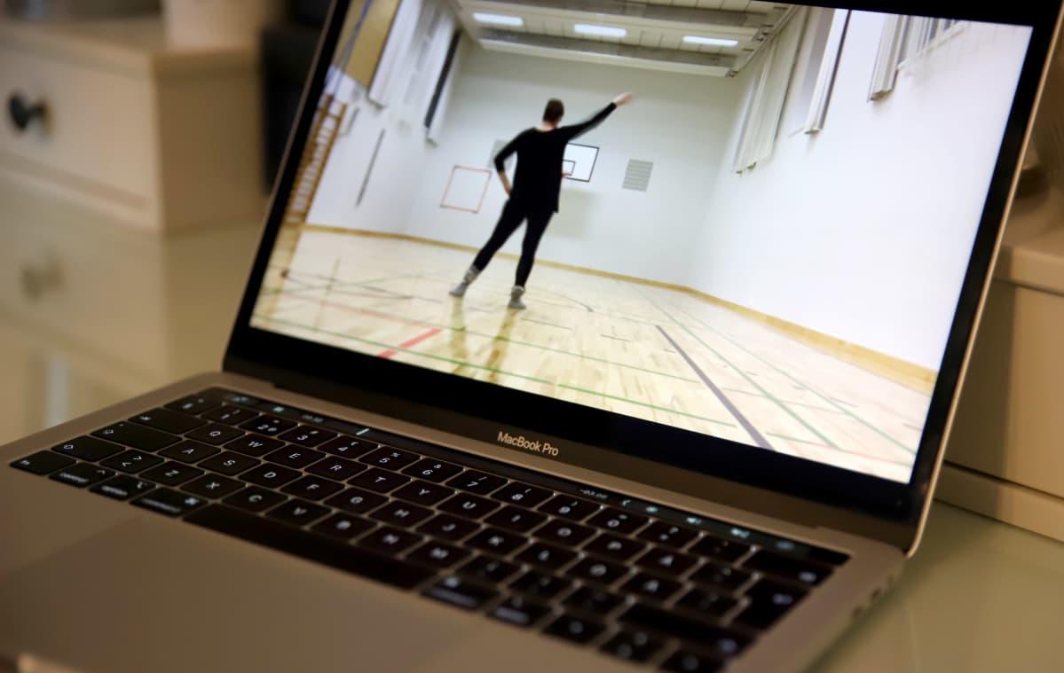 tietokoneen näytöllä video, jossa opettaja näyttää tanssikuviot tyhjässä jumppasalissa