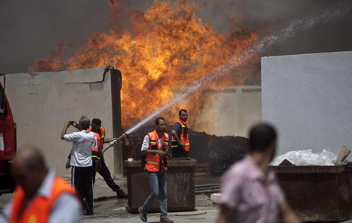 Palomiehet yrittivät sammuttaa läntisessä Gaza Cityssä sijaitsevan YK:n varastorakennuksen paloa Israelin ilmaiskun jäljiltä 12. heinäkuuta 2014.