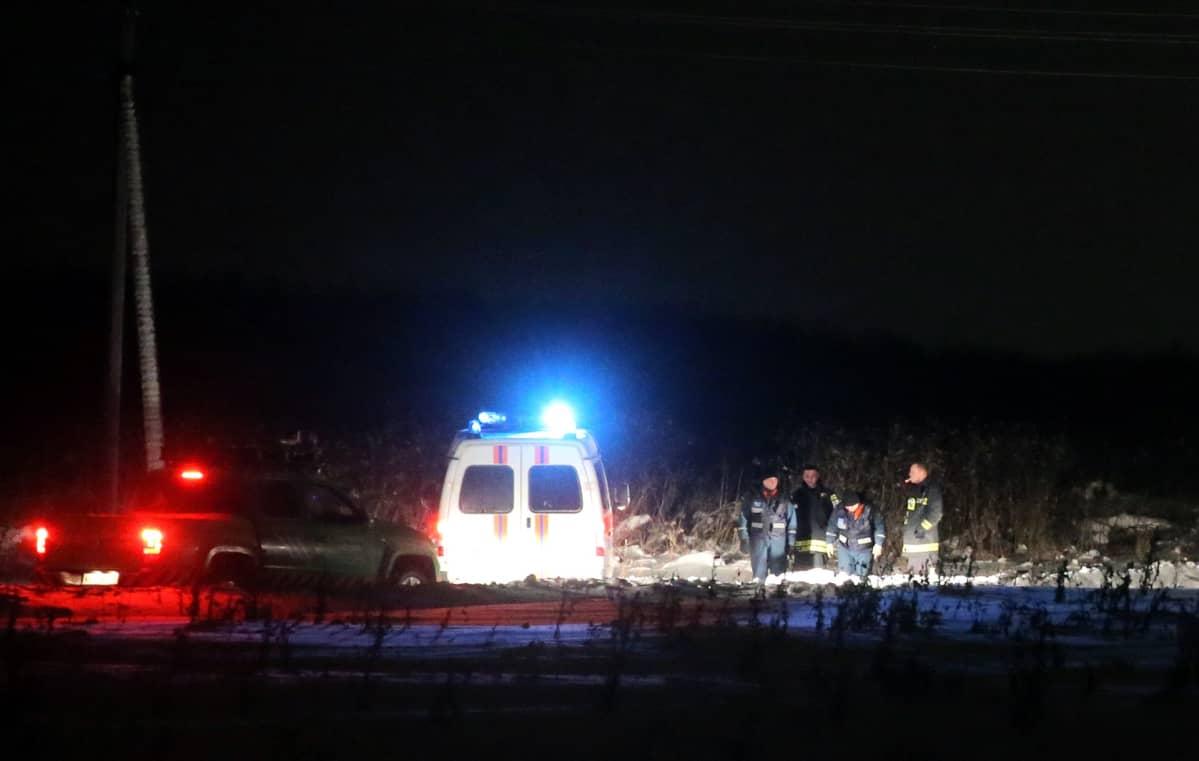 Kuvassa neljä pelastustyöntekijää, ambulanssi ja avolava-auto. Lähellä koneen maahansyöksypaikkaa.