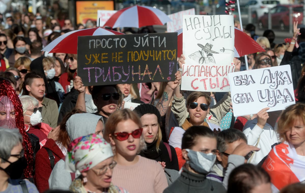 Naisia mielenosoitusmarssilla kyltteineen.