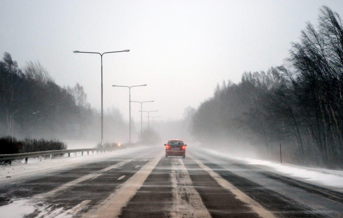 Auto moottoritiellä, lumisade, lymipyry, pöllyävä lumi