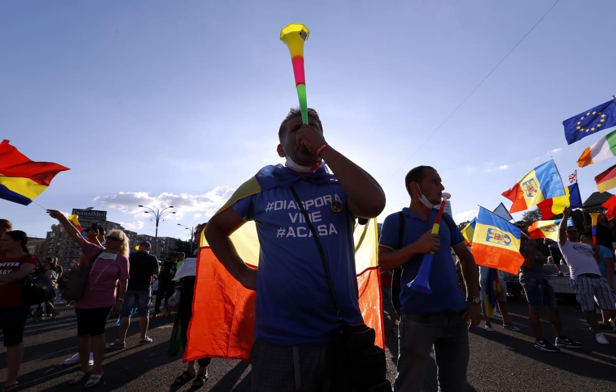 Mielenosoittajilla on mukana Romanian ja EU:n lippuja, muovisia torvia ja tekstilakanoita.
