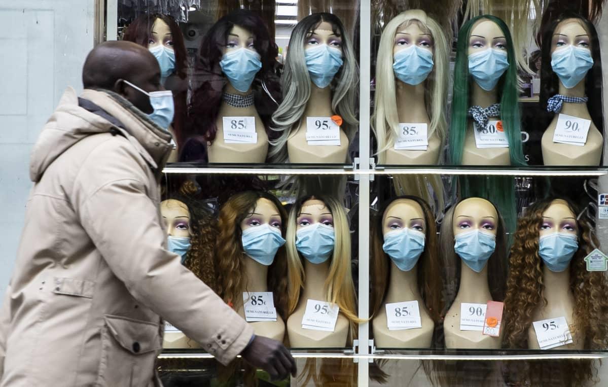 Kasvomaskilla suojautunut mies kulki Pariisissa keskiviikkona kaupan näyteikkunan ohitse, ikkunassa oli nukeilla maskit myös kasvoilla.