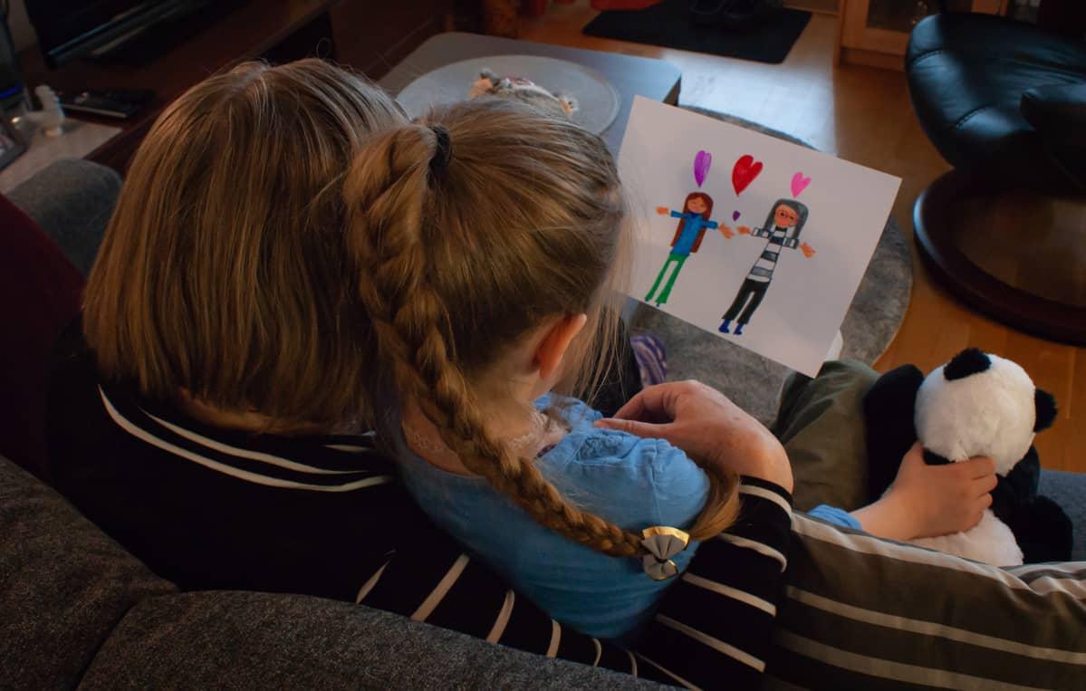 Seija Vahvelainen istuu sohvalla tyttärentyttärensä kanssa.