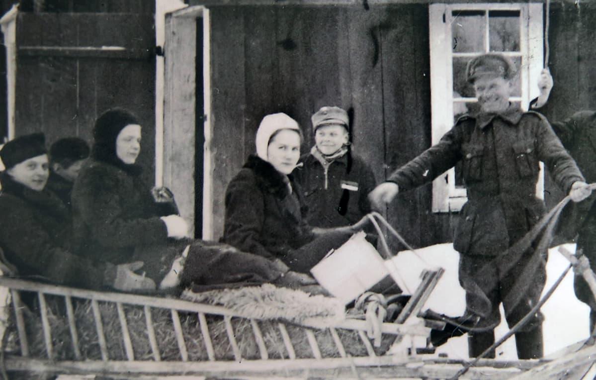 Vanha valokuva, jossa on naisia reessä.