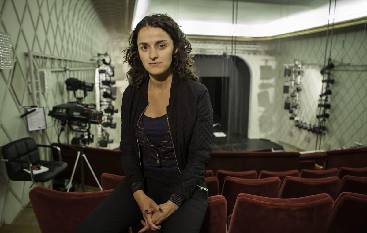 Esra istuu teatterin katsomon penkinnojalla selkä lavalle päin. Hänen kiharat hiuksensa ovat auki ja yltävät olkapäille. Taustalla näkyy tyhjä esiintymislava, valaisimia ja suuri videokamera.