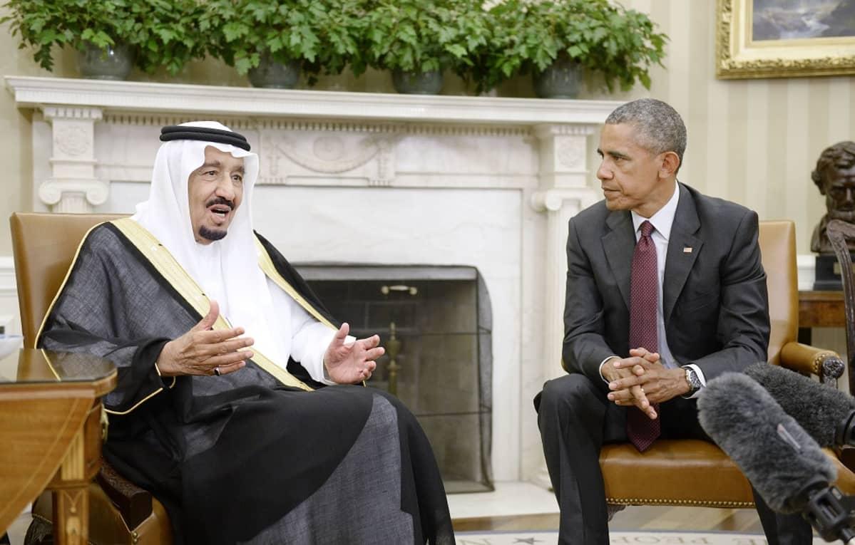 Kuningas Salman puhuu ja presidentti Obama kuuntelee. Miehet istuvat tuoleissa takan edessä. Kuvan etualalla näkyy toimittajien mikrofoneja.
