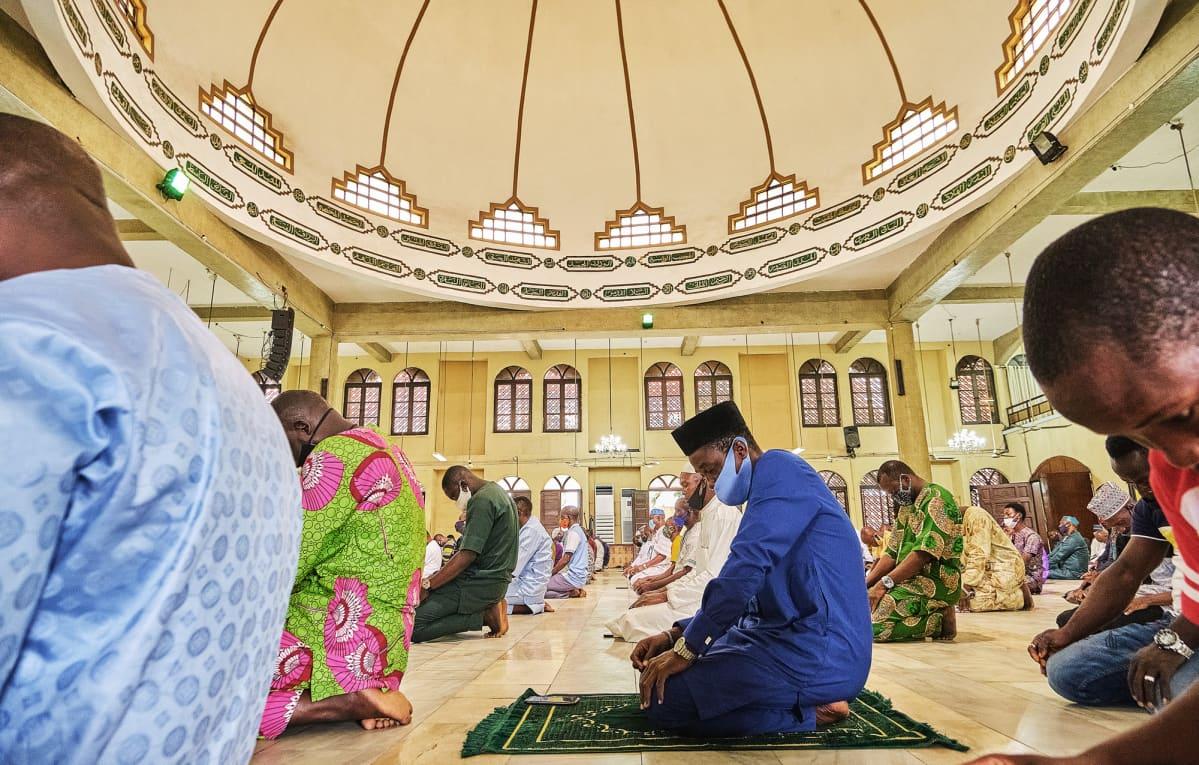 Nigerialaisia ihmisiä hengityssuojaimet kasvoilla rukoilemassa moskeijassa.