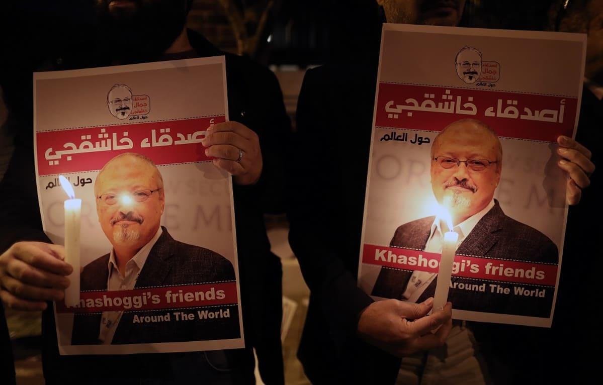Ihmisten käsissä Khashoggin kuvia ja kynttilöitä.