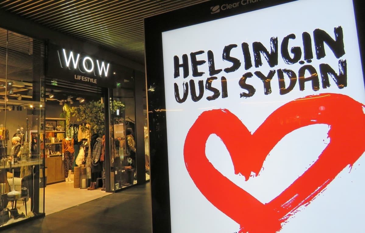 """Edessä mainostaulu, jossa sydän ja teksti """"Helsingin uusi sydän"""". Takana vaatekauppa, jonka oven päällä nimi Wow Lifestyle,"""