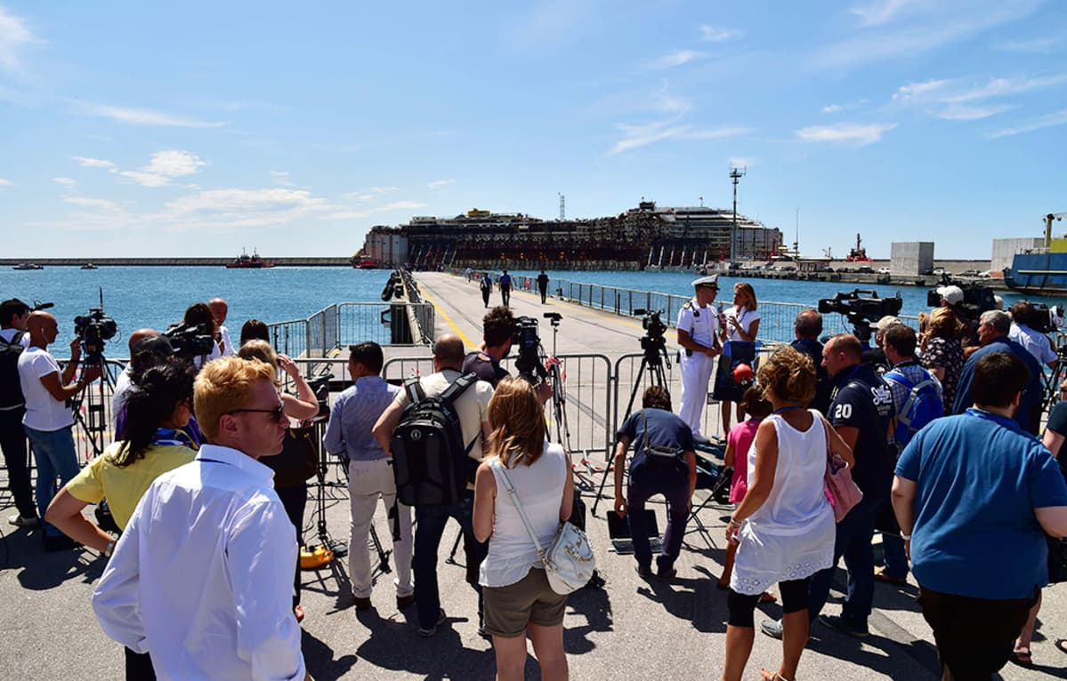 Joukko toimittajia ja kuvaajia kokoontui Genovan satamaan seuraamaan Costa Concordian onnistunutta hinausoperaatiota.