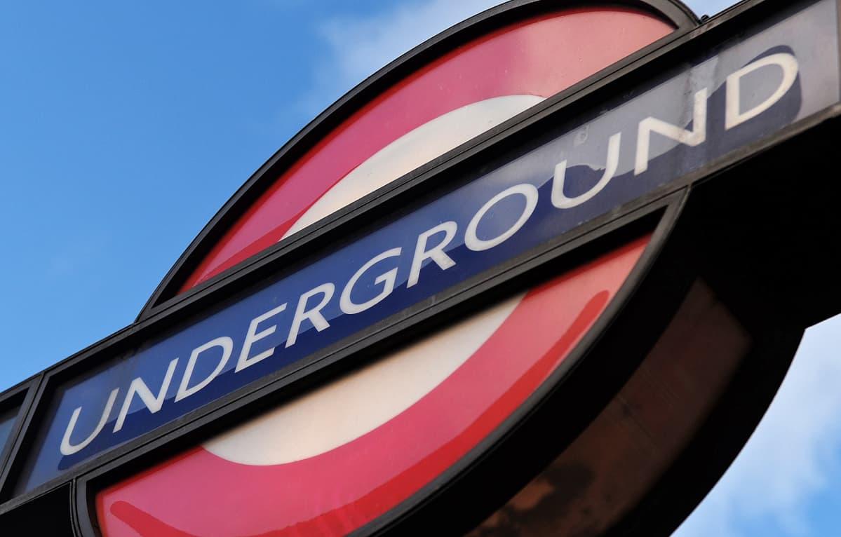 Lontoon metron tunnuskyltti. Punavalkoisen kyltin keskellä lukee sinisellä pohjalla UNDERGROUND.