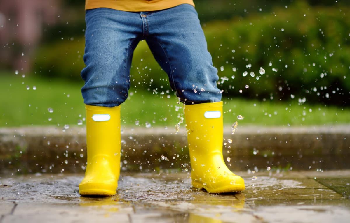Lapsi hyppää vesilätäkköön kumisaappaat jalassaan.