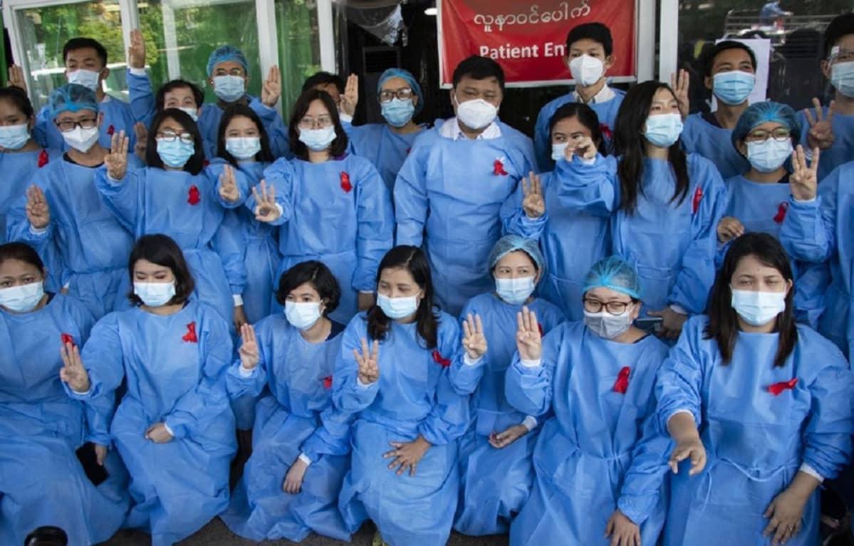 Kuvassa lääkintähenkilöstöä. Heillä on työvaatteissaan punaisia nauhoja.