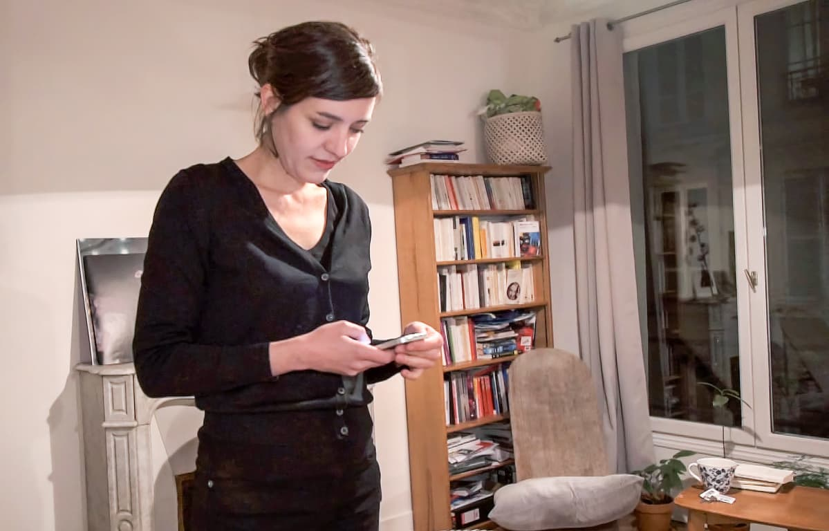 nainen katsoo kännykkäänsä
