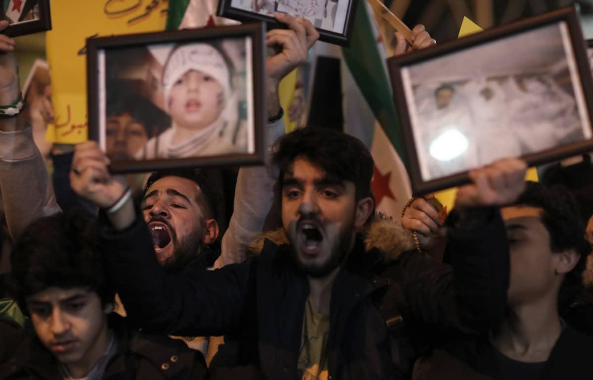 Mielenosoittajat pitävät käsissään kaasuiskun uhrien valokuvia.