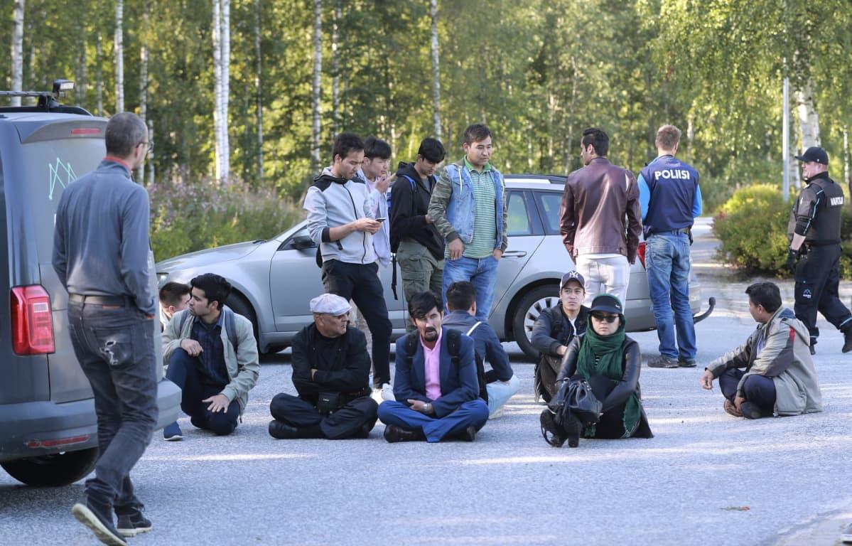 ihmiset istuvat tiellä