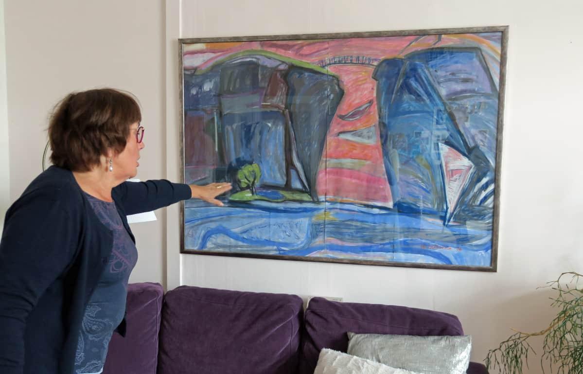 Leena-Riitta Salminen  osoittaa maalaamaansa taulua