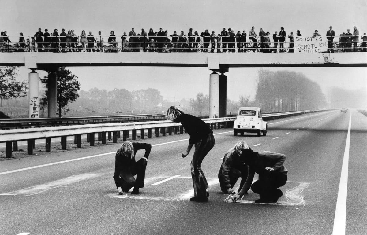 Ihmiset piirtelevät moottoritiehen.