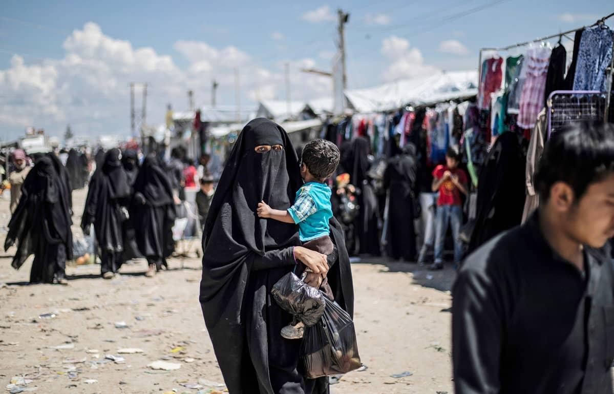 Nainen kantaa lasta Al-Holin leirillä 18. huhtikuuta