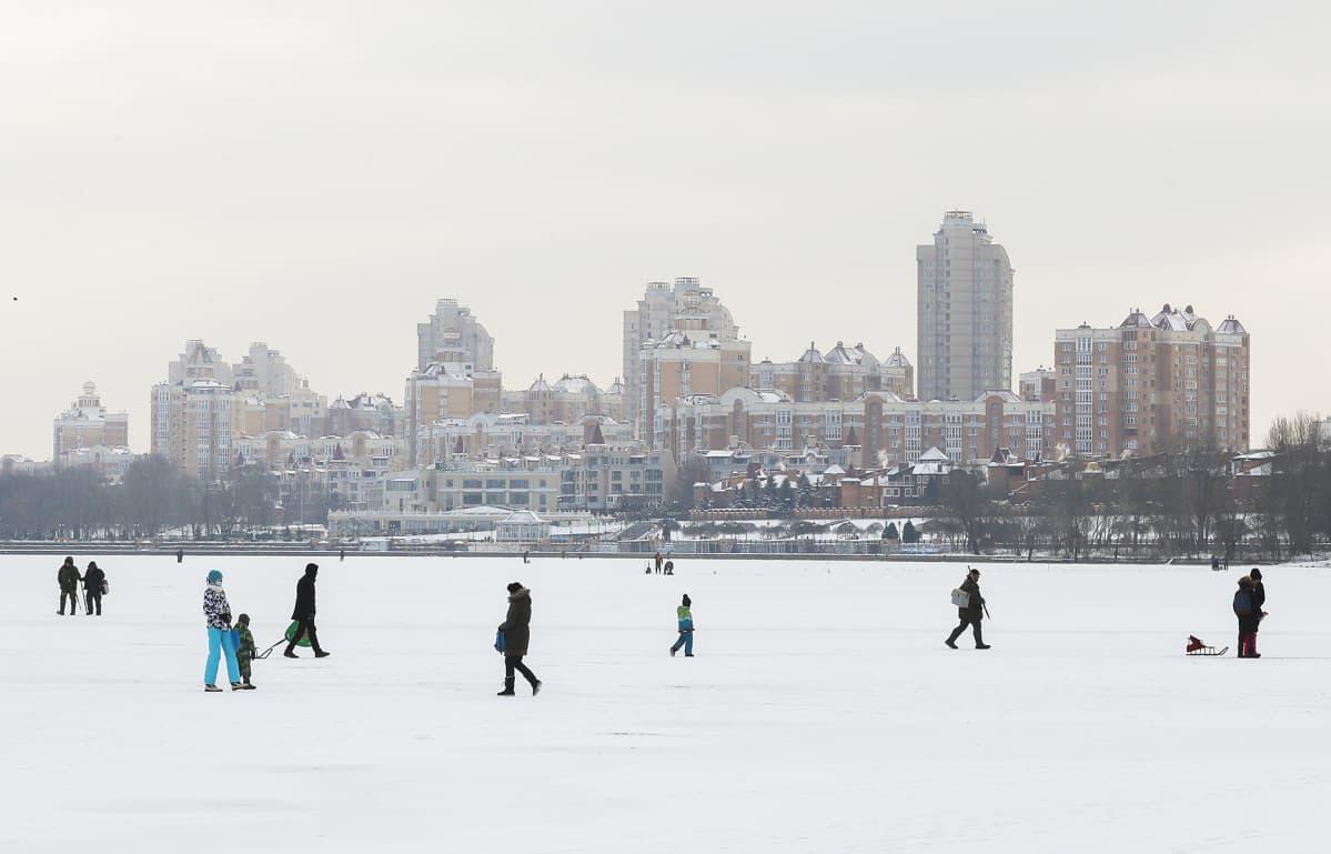 Ihmisiä kävelmässä joen jäällä Kiovassa tammikuussa 2021.