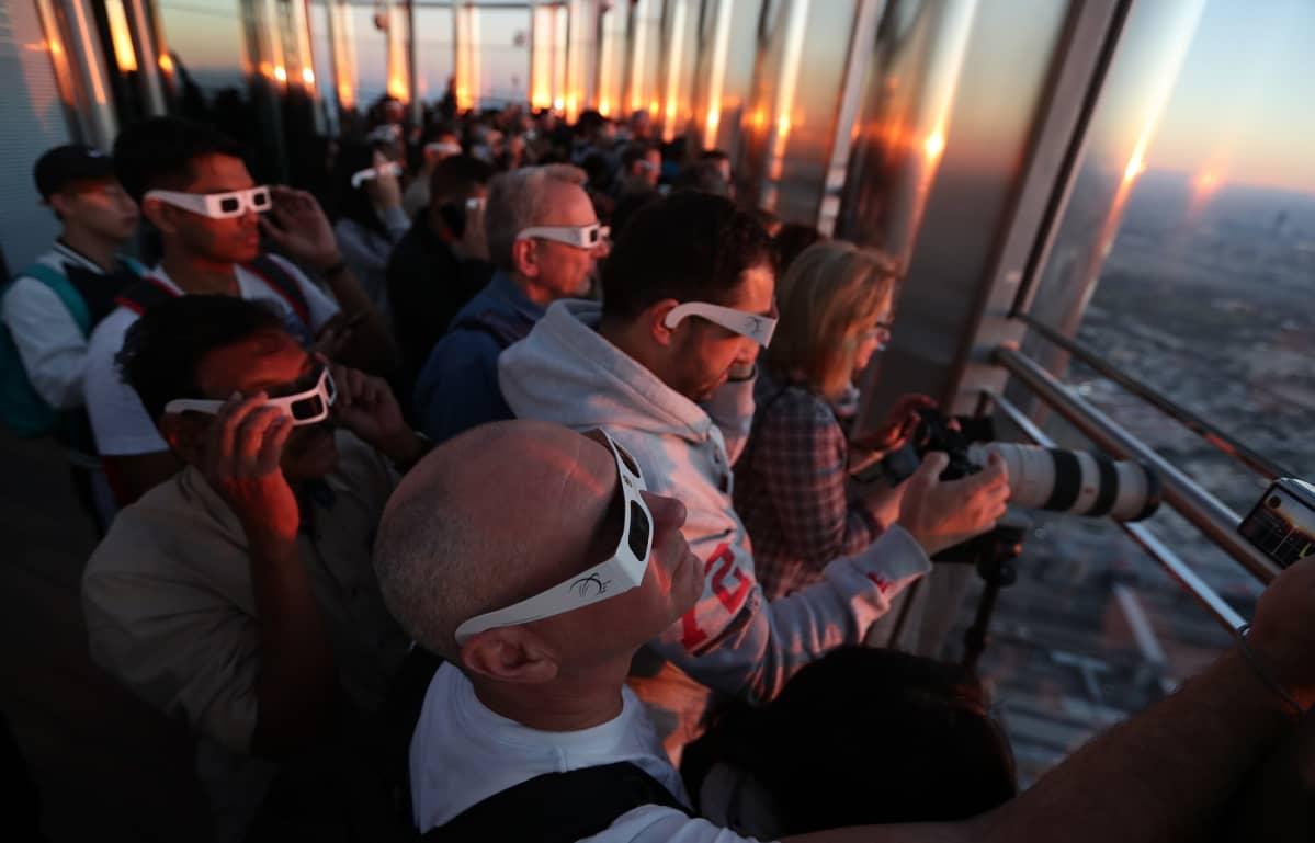 Ihmiset ihastelivat rengasmaista auringonpimennystä Burj Khalifa -pilvenpiirtäjän korkeuksissa Dubaissa.