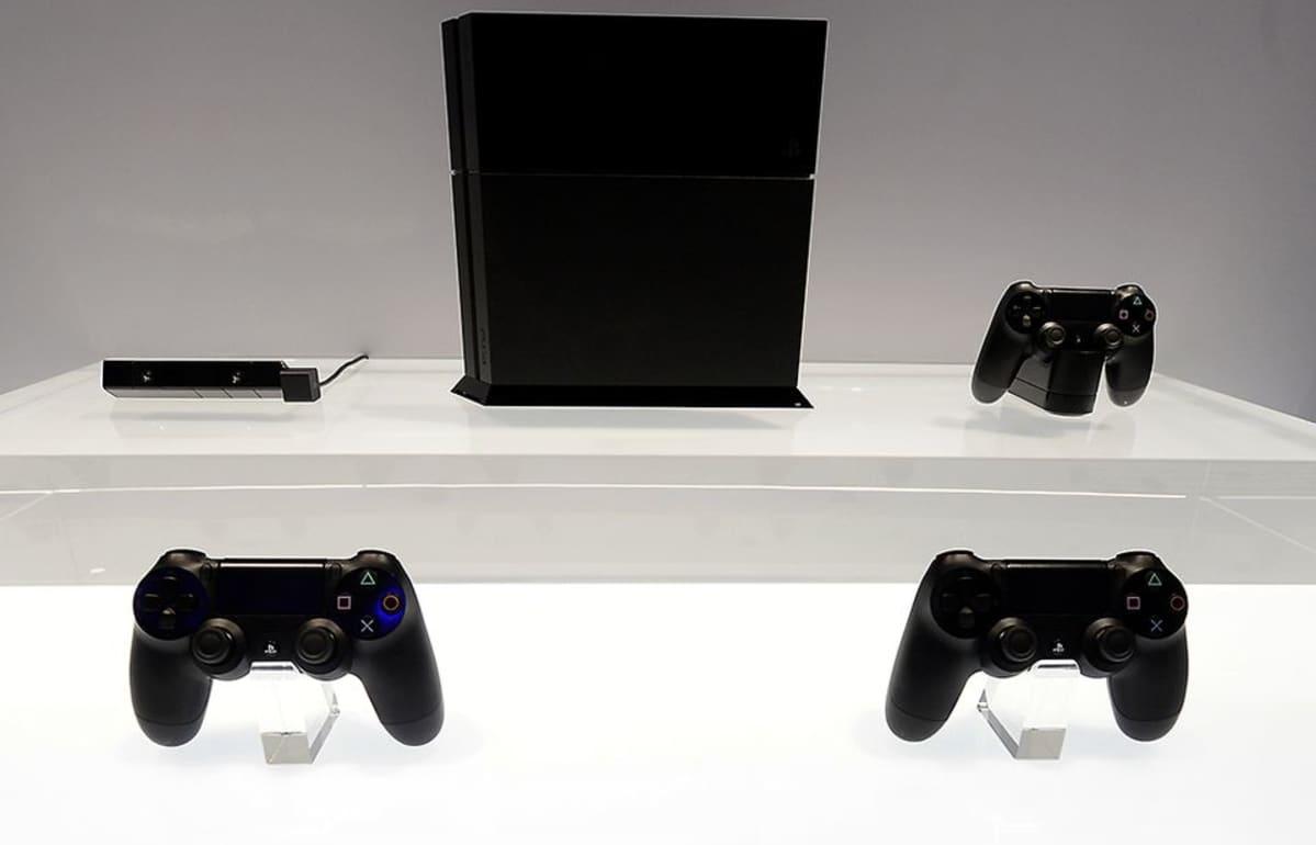 Väriltään musta playstation 4 -pelikonsoli ja  mustia peliohjaimia esillä E3-messuilla kirkkaan valkoista alustaa vasten.