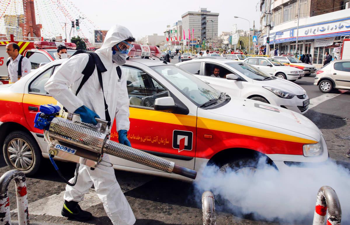 Palomies desinfioi katua Iranin pääkaupungissa Teheranissa perjantaina.