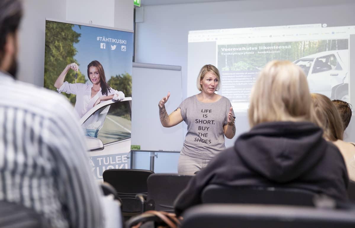 Autokoulun opettaja Minttu Vänni puhuu luokan edessä.