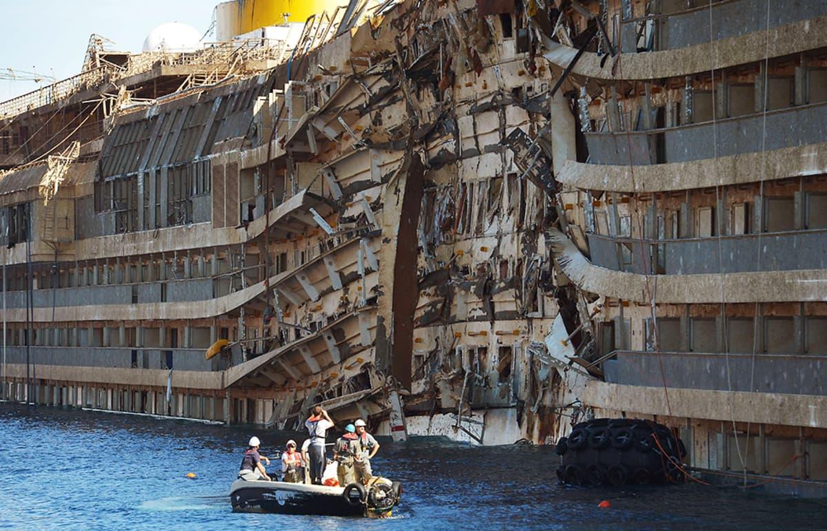 Miehiä veneessä Costa Concordian hylyn vierellä.