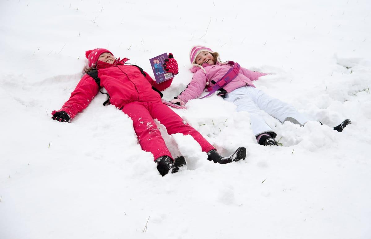 Lapset makaavat lumessa.