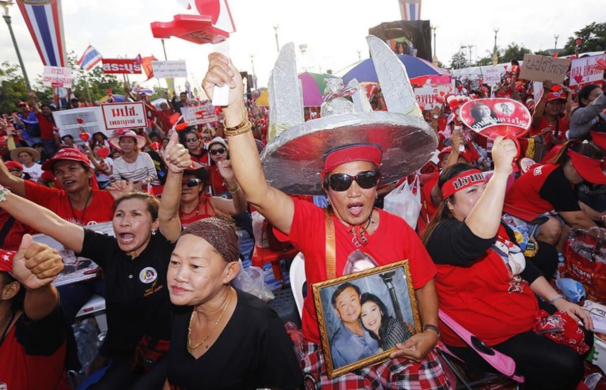 Mielenosoittajan pitelemässä valokuvassa näkyy Thaimaan syrjäytetty pääministeri Thaksin Shinawatra (vas.).