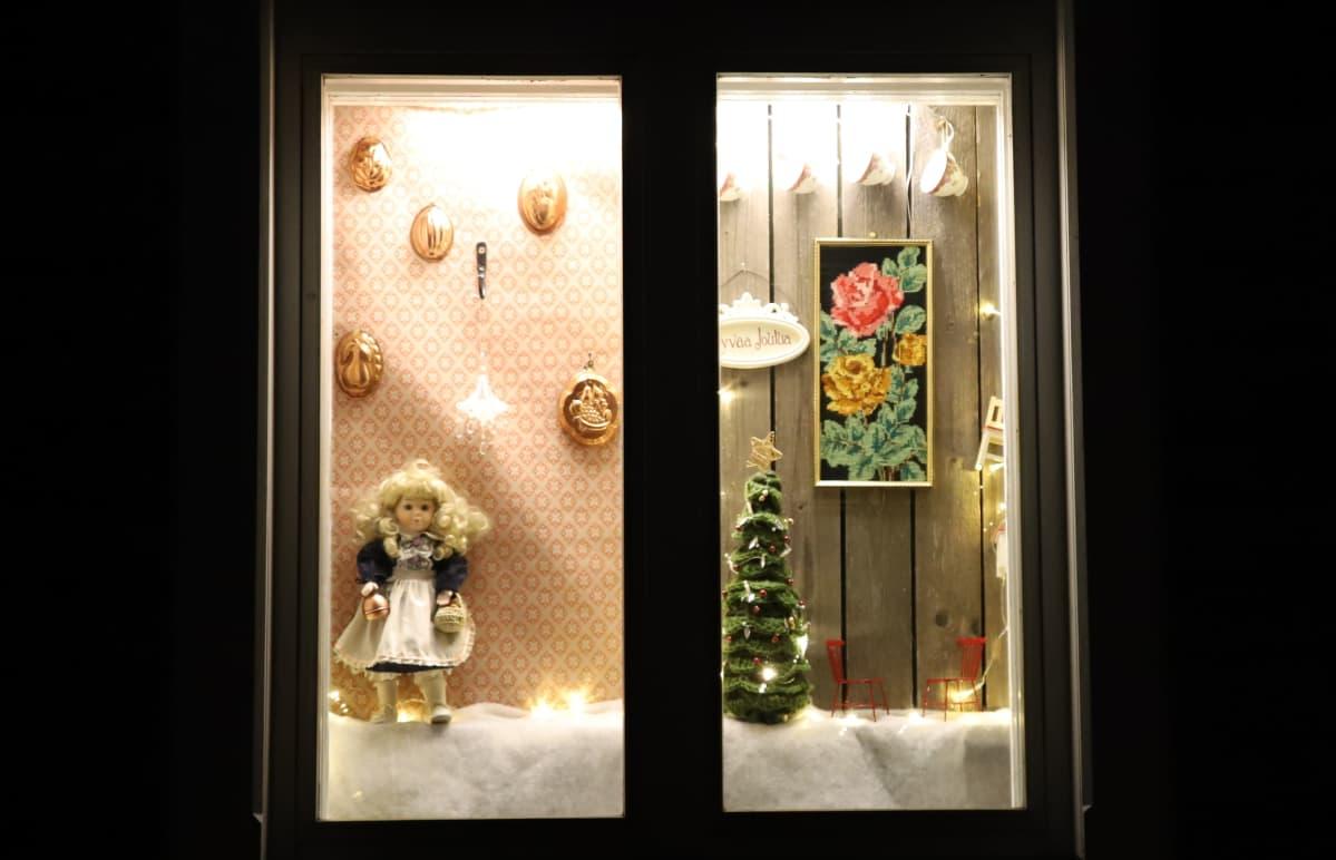 nukke, tauluja ja joulukuusi ikkunalla