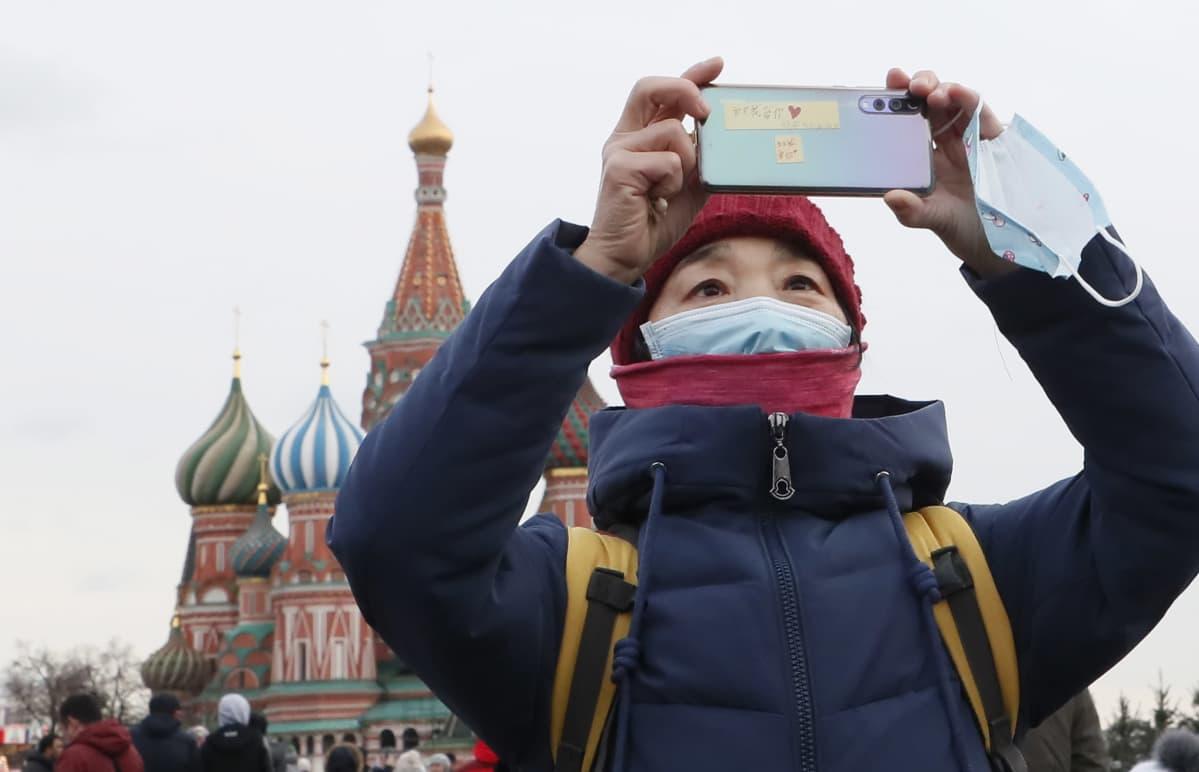 Kiina rajoittaa ryhmämatkoja ulkomaille maanantaista lähtien. Nainen otti kuvia Moskovan Punaisella torilla 26. tammikuuta.