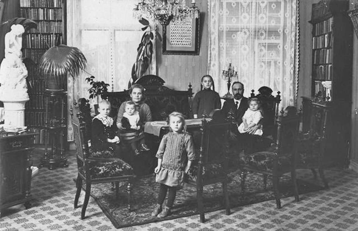 Mustavalkoinen valokuva porvariskodin ruokasalista. Kristallikruunun alla ruokapöydän ympärillä nainen, mies ja viisi lasta, iältään kahdesta vuodesta seitsemään.