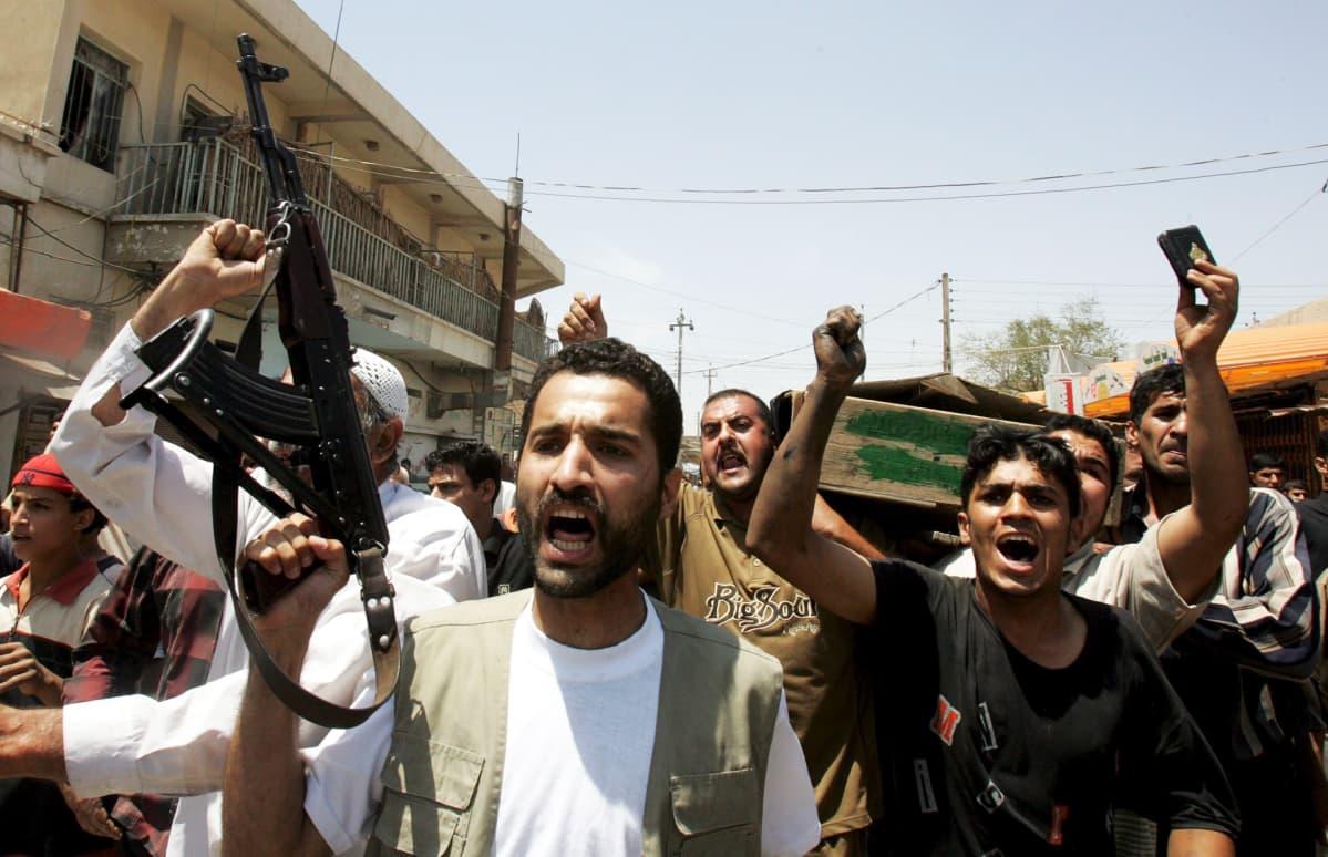 Sunnimiehet kantavat shiiojen ja sunnien välisissä väkivaltaisuuksissa kuolleen miehen arkkua hautajaisissa toukokuussa 2005 Bagdadissa.