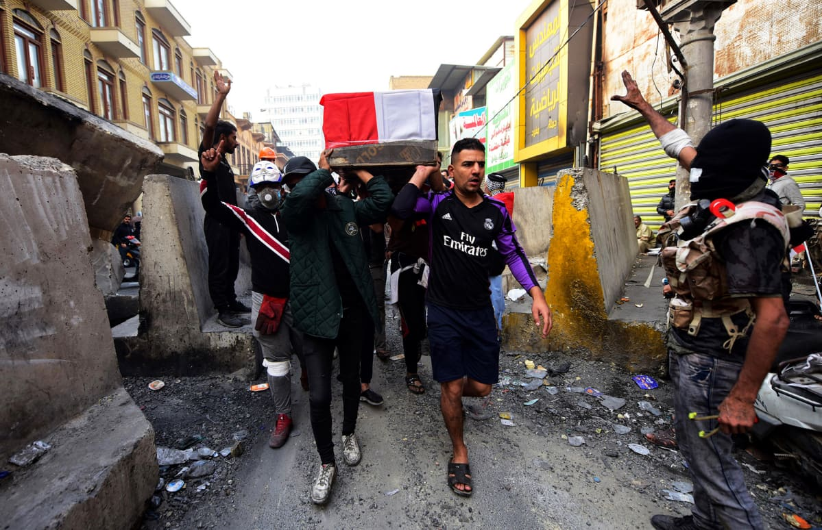 Irakilaiset kantavat turvallisuusjoukkojen tapaaman protestoijan arkkua Bagdadissa.