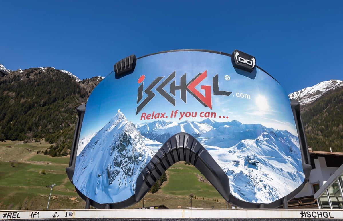 Laskettelulasien muotoinen mainostaulu, jossa lukee Ischgl, rentoudu jos pystyt...
