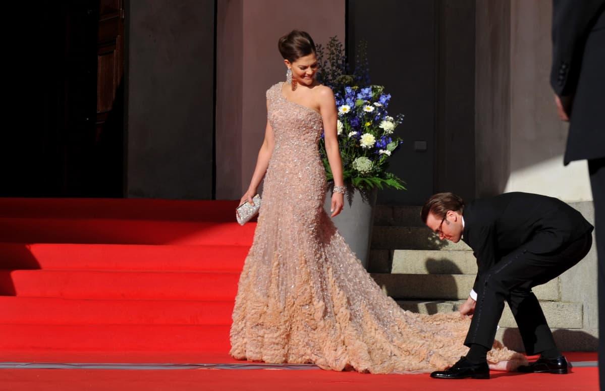 Daniel on kumartunut korjaamaan Victorian puvun pitkää laahusta.