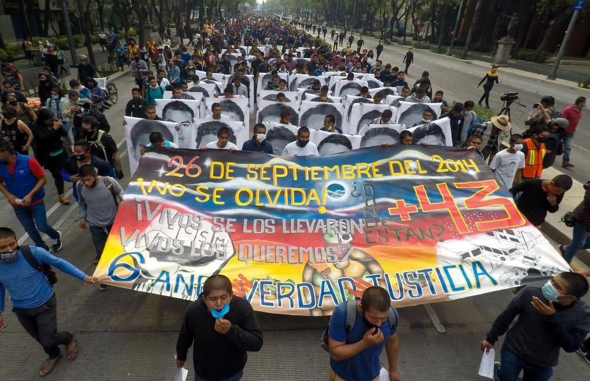 Ihmisjoukko kantaa suurta mielenosoituslakanaa.