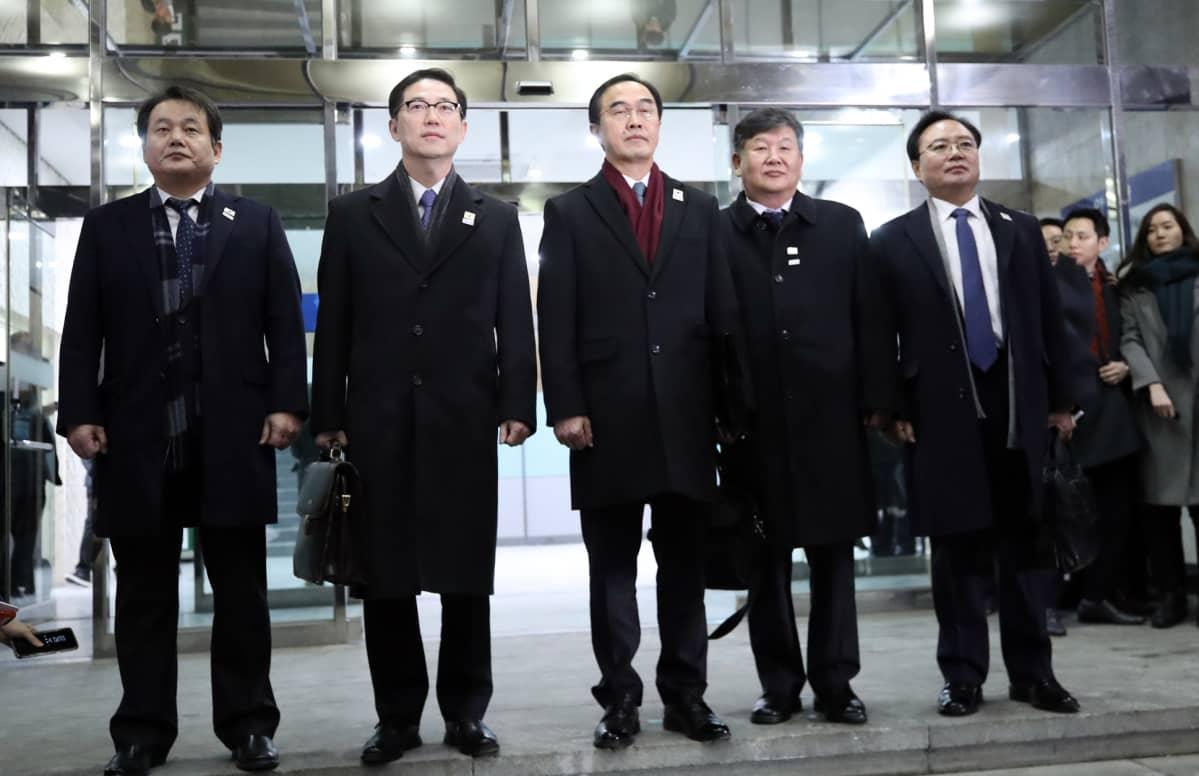 Viisi mustapukuista, vakavaa miestä poseeraa kameralle.