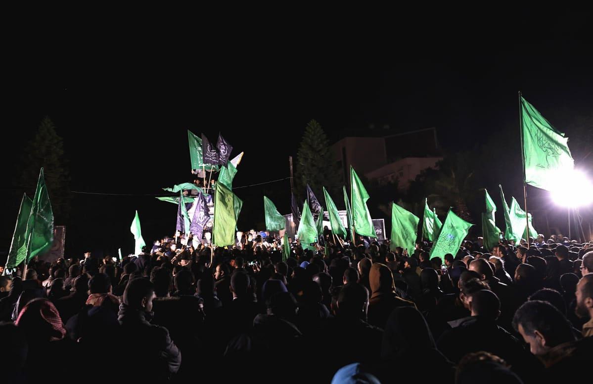 Kuvassa pimeä, ihmisjoukko kantaa vihreitä lippuja valonheitinten valossa