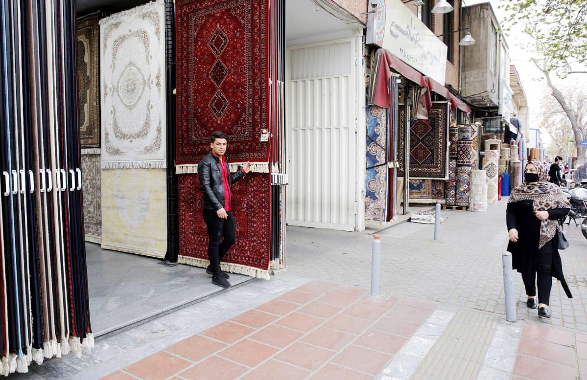 Iranialainen mattokauppias seisoo mattokaupan edustalla Teheranissa.