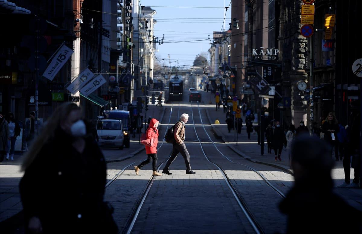 Jalankulkijoita ylittämässä Aleksanterinkatua Helsingissä 3. maaliskuuta 2021.