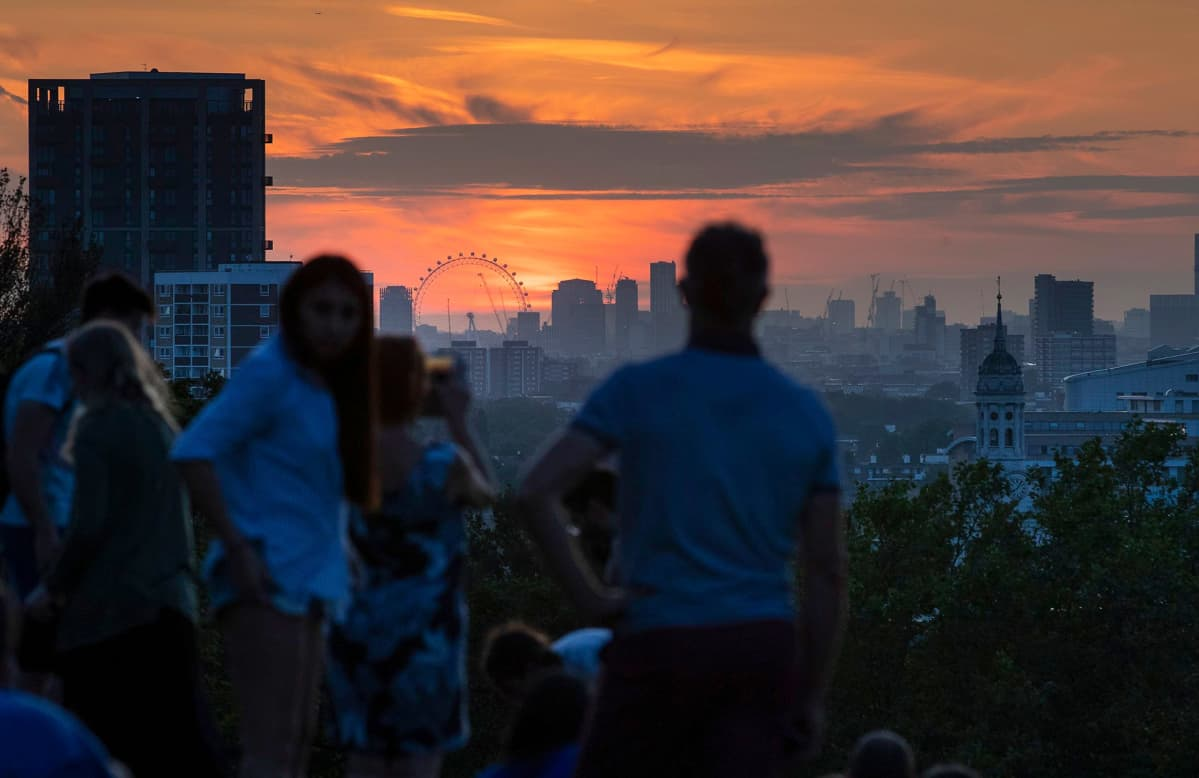 Ihmiset katsovat auringonlaskua Lontoossa.