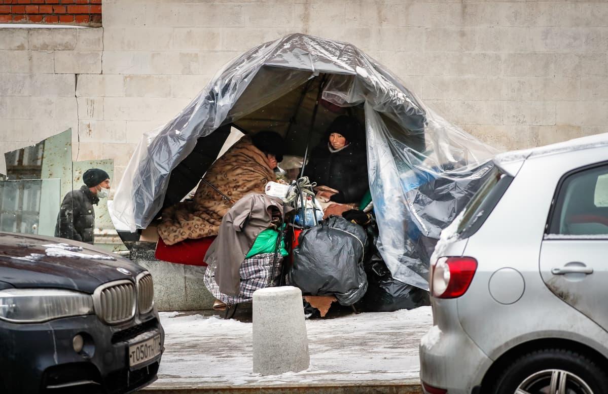 Koditon nainen on muovista tehdyn katoksen alla.