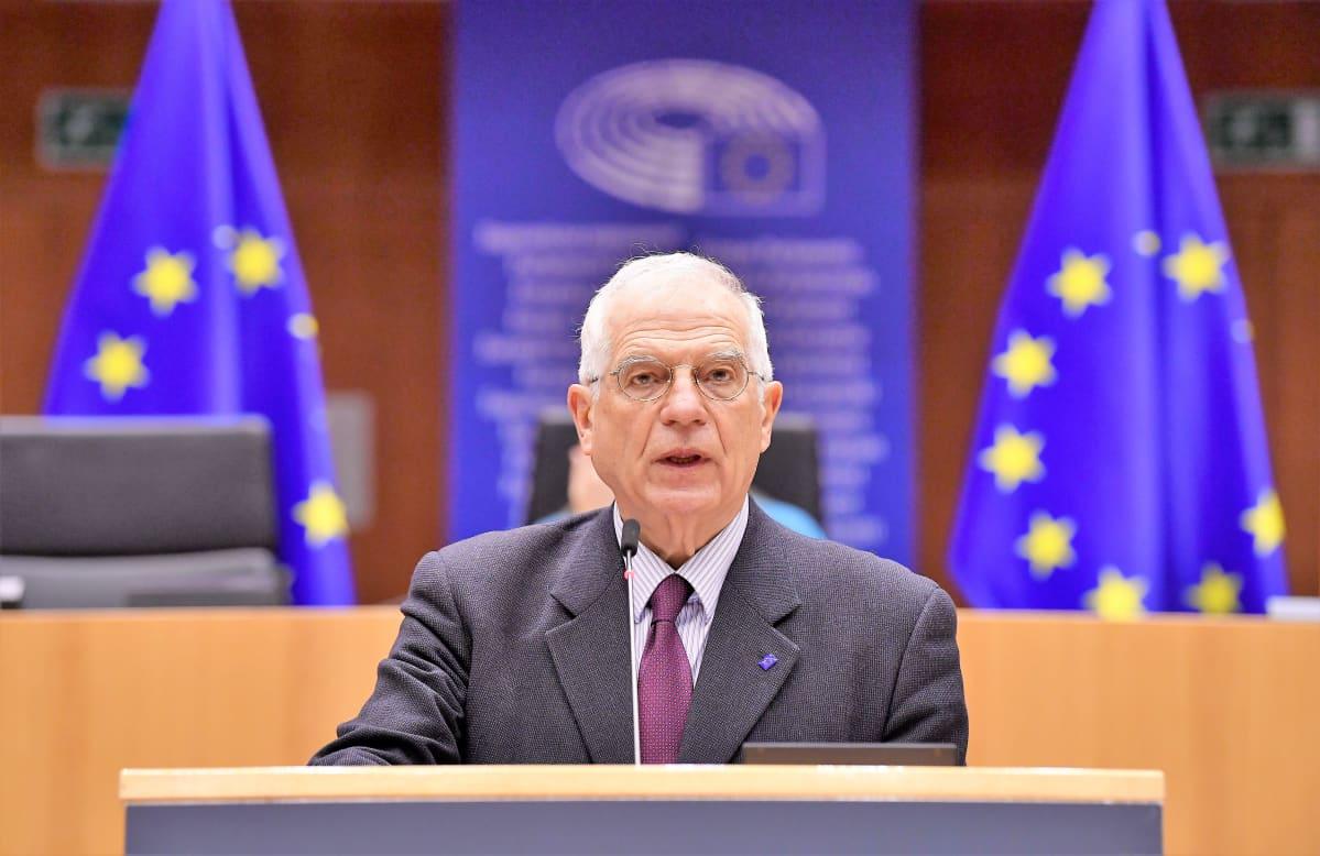 Josep Borrell puhuu puhujanpöydän takana salissa. Hänellä on harmaa puku ja violetti kravatti. Takana ylemmällä korokkeella näkyy kaksi EU:n lippua.
