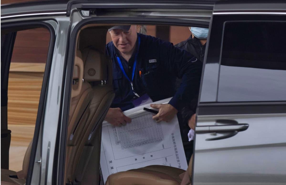 Lippalakkipäinen mies astumassa autoon. Hänellä on kädessään kynä ja iso paperiarkki, jossa on sarakkeita.