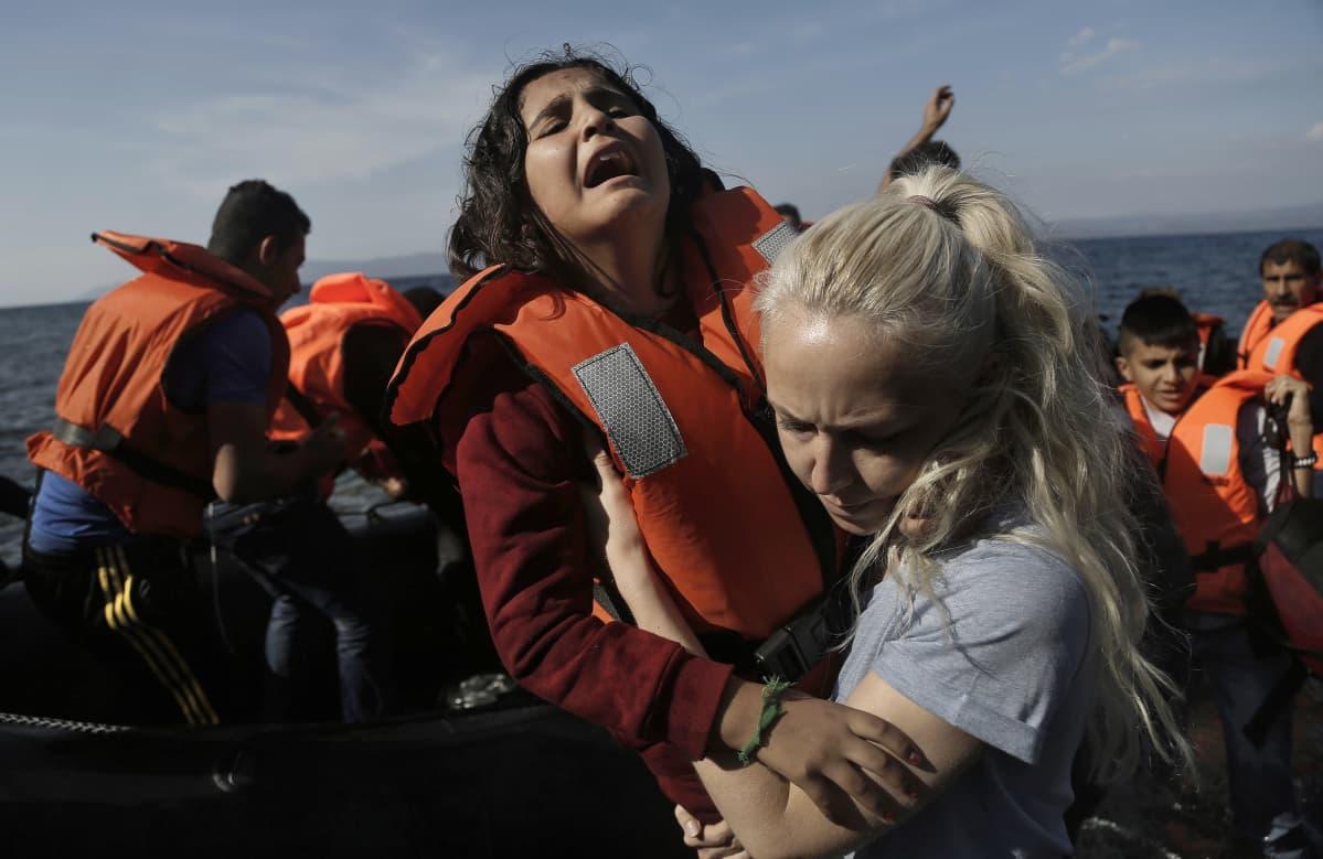Itkevää tyttöä nostetaan syyrialaisia kuljettaneesta venestä Lesboksen saarella.