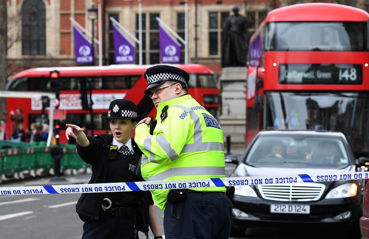 Kaksi poliisia keskustelee, taustalla Lontoon busseja.